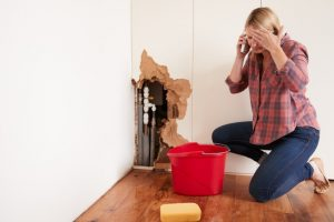woman with burst water pipe calling a plumber