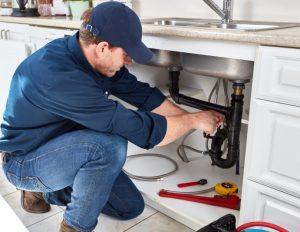 plumber fixing garbage disposal clog